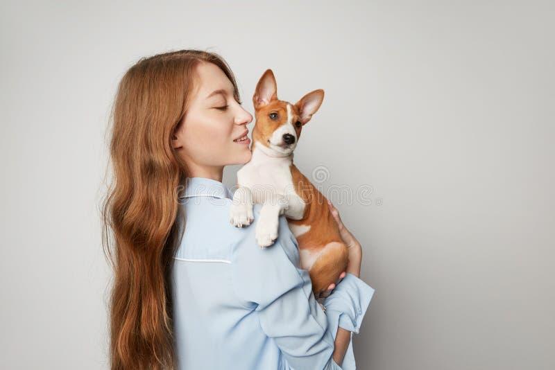 Śliczny młodej kobiety przytulenie, całowanie i jej szczeniaka basenji pies Miłość między psem i właścicielem pojedynczy białe tł obraz royalty free