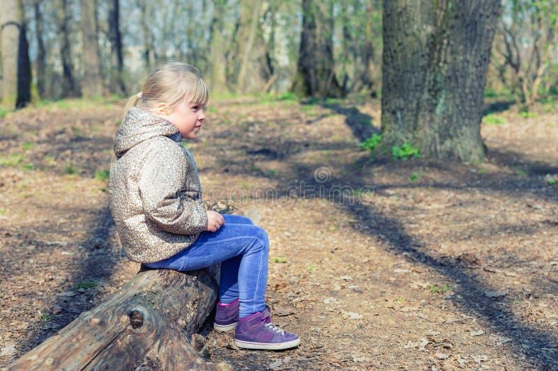Śliczny mały caucasian blond dziewczyny sittng na drewnianym nazwa użytkownika lesie, patrzeć gdzieś i Uroczy zadumany dziecko ma zdjęcia stock