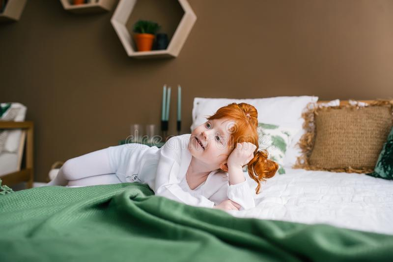 Śliczny szczęśliwy rudzielec berbecia dziewczyny lying on the beach w łóżku w domu zdjęcia royalty free