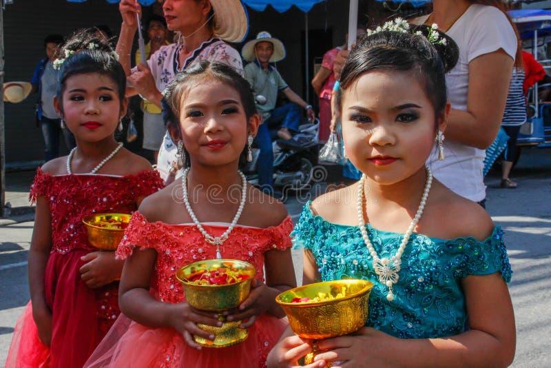 Ślubna ceremonia na ulicie Trzy małej Tajlandzkiej dziewczyny z makijażem w eleganckich sukni chwyta kwiatach i obraz stock