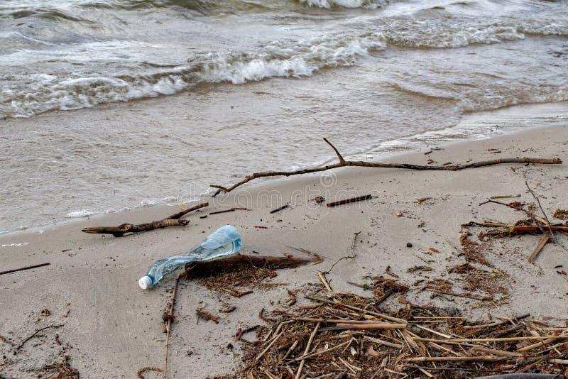 Śmiecący krawędzią jezioro plastikowymi butelkami Zanieczyszczający środowisko w lasowym terenie obraz stock