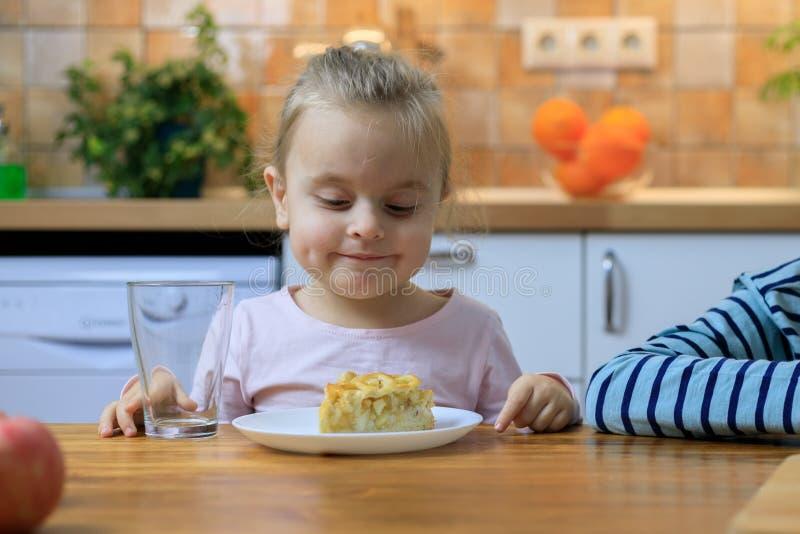 Śmieszna mała dziewczynka je jabłczanego kulebiaka w domu zdjęcia stock