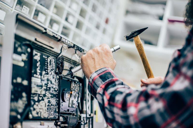 Śmiesznej elektryka inżyniera naprawy komputerowy monitor z młotem i śrubokrętem obraz stock