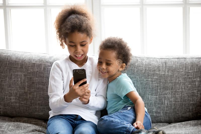 Śmieszni mali czarni dzieciaki zabawę bawić się na smartphone zdjęcia royalty free