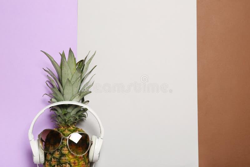 Śmieszny ananas z hełmofonami i okularami przeciwsłonecznymi na koloru tle, odgórny widok fotografia stock