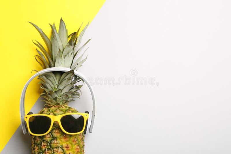 Śmieszny ananas z hełmofonami i okularami przeciwsłonecznymi na koloru tle, odgórny widok fotografia royalty free