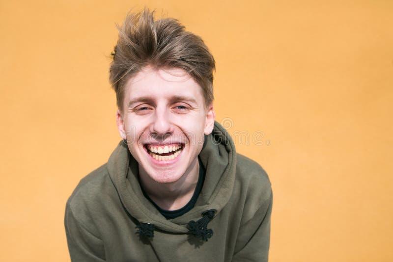 Śmieszny facet patrzeje w uśmiechy i kamerę przeciw tłu pomarańcze ściana zdjęcia stock