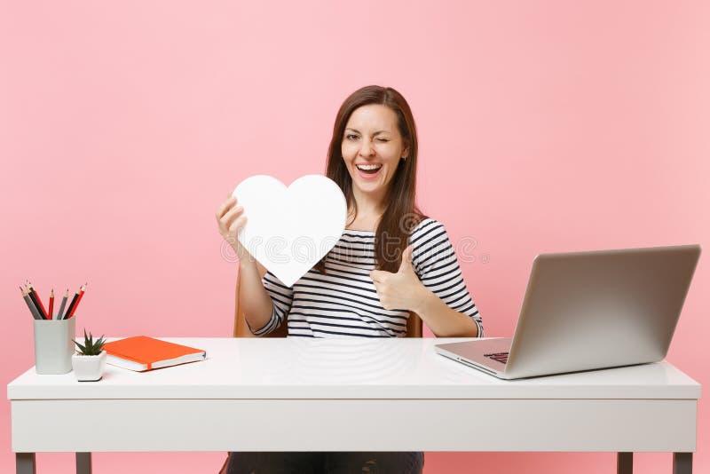 Śmieszny kobiety mruganie pokazuje kciuk w górę trzymać białego serce z kopii przestrzenią pracuje na projekcie podczas gdy siedz obrazy stock