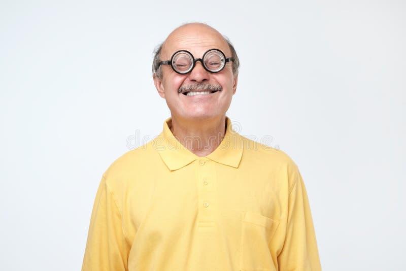 Śmieszny starszy mężczyzna jest ubranym głupich szkła patrzeje kamerę zdjęcia stock