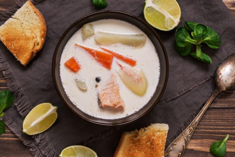 Śmietankowa łososiowa polewka z grulami i marchewkami słuzyć z grzanką na drewnianym nieociosanym deska stole Fiński rybi zupny k zdjęcie royalty free