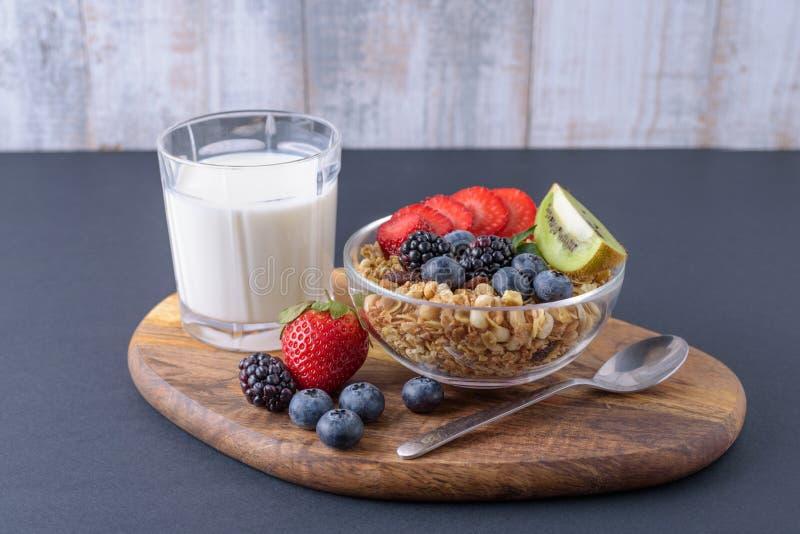Śniadanie granola z jagodami i szkłem mleko na drewnianej desce obrazy stock