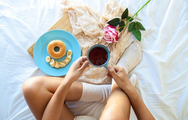 Śniadanie w łóżku Kobieta pije kawę w jej łóżku w domu podczas gdy sprawdzać jej laptop obraz royalty free