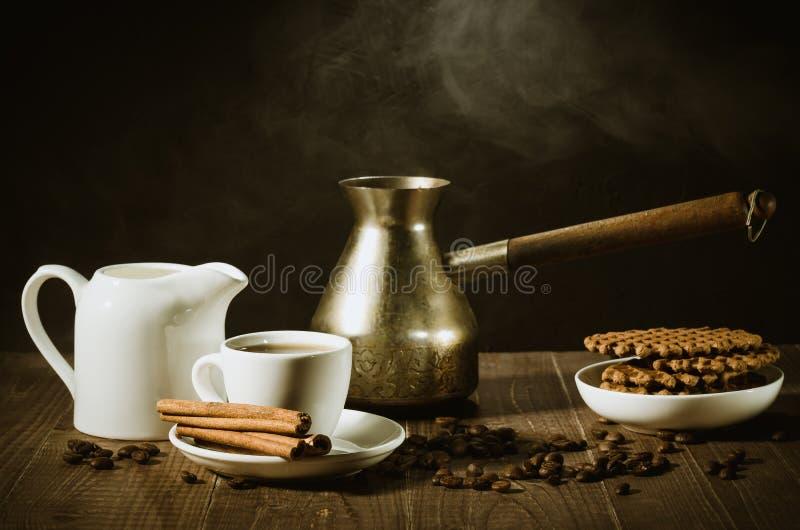 Śniadanie z kawą, ciastkami i ciastkami na drewnianym stole/filiżanka z cynamonem, starymi garnka, creameru i czekolady, zdjęcie royalty free
