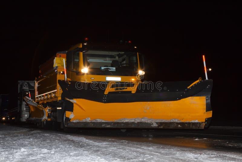 Śnieżny pług przy nocą na śliskiej drodze fotografia stock