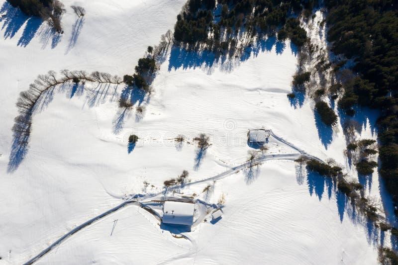 Śnieg zakrywał daleką chałupę, farmę w górach i śnieżną drogę, fotografia stock