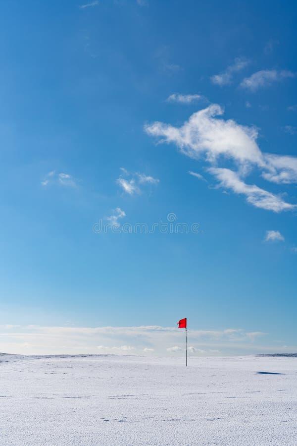 Śnieg zakrywał opustoszałą golf zieleń z czerwoną flagą, na Cleeve wzgórzu, Cotswolds, Gloucester UK fotografia royalty free