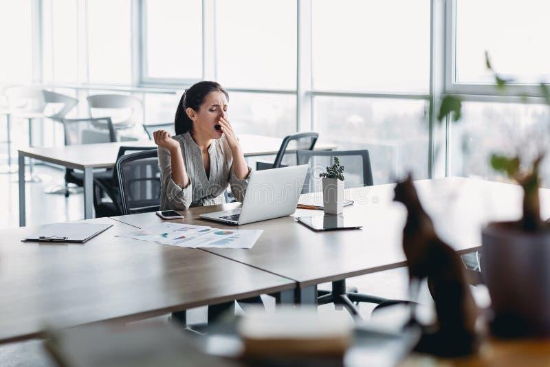 Śpiący młody biznesowej kobiety obsiadanie przy biurowym biurkiem, pracujący z laptopem i ziewaniem zdjęcie royalty free