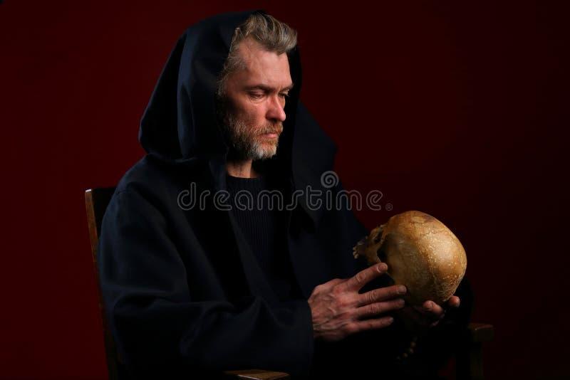 Średniowieczny michaelita w czarnym kontuszu z czaszką w jego ręki fotografia stock