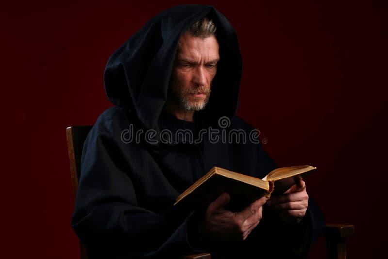 Średniowieczny michaelita w czarnym kontuszu z książką w jego ręki zdjęcia royalty free