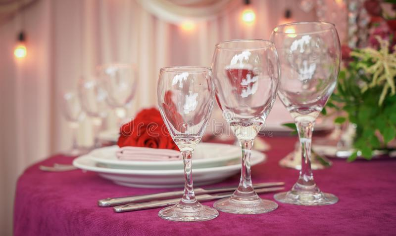 Świąteczny ślubu stołu położenie z czerwień kwiatami, pieluchami, rocznika cutlery, szkłami i świeczkami, jaskrawy lato stołu wys obrazy stock
