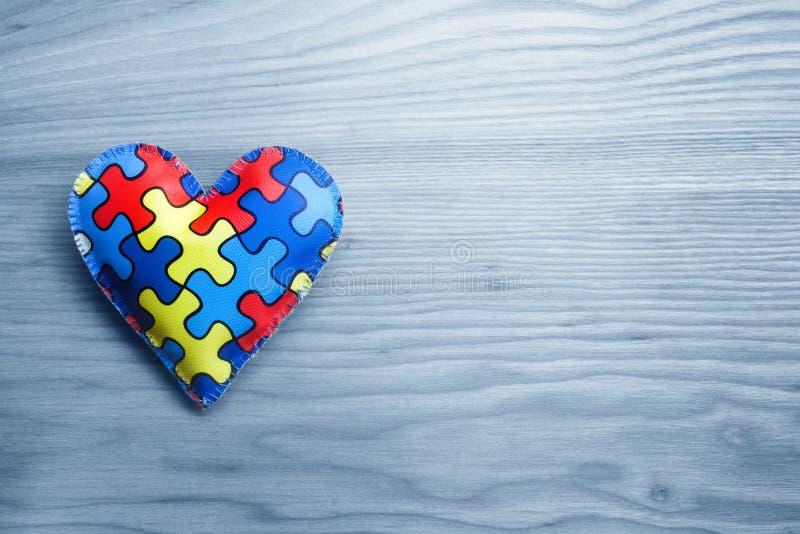 Światowy autyzm świadomości dzień, umysłowy opieki zdrowotnej pojęcie z łamigłówką lub wyrzynarka wzór na sercu, obrazy stock