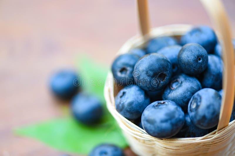 Świeże czarne jagody owocowe w kosza i zieleni liściach na drewnianym tle fotografia stock
