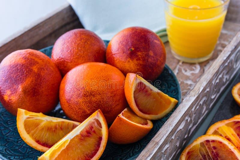 Świeże Soczyste Krwionośne pomarańcze Całe i Pokrojone na talerzu i tacy z sokiem pomarańczowym w tle fotografia royalty free