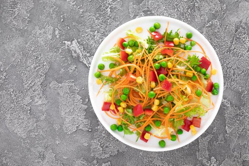 Świeżego warzywa sałatka z surową marchewką, zielonymi grochami, kukurudzą, słodkim pieprzem i sałatą, Zdrowy weganin, jarski lun fotografia royalty free