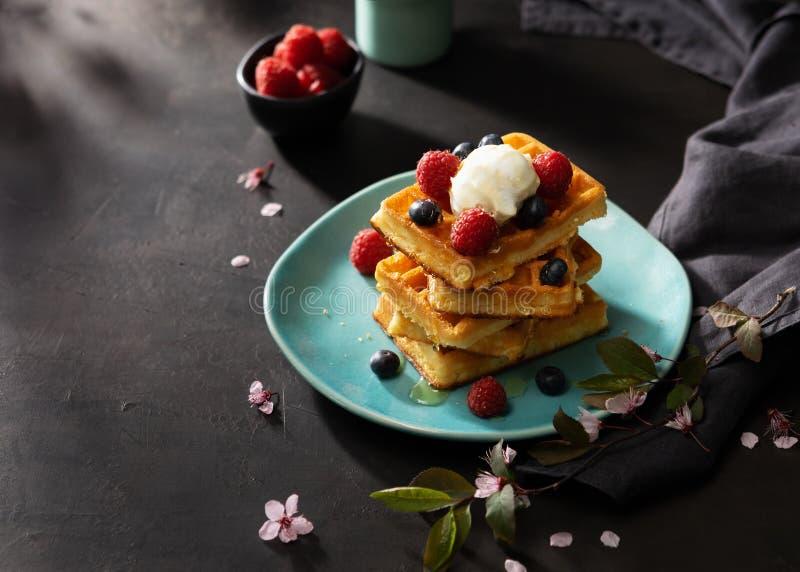 Świeżo piec gofry z malinkami, jagodami, miodem, kawą dla śniadania i śniadanio-lunch na ciemnym tle z kopii przestrzenią, obraz stock