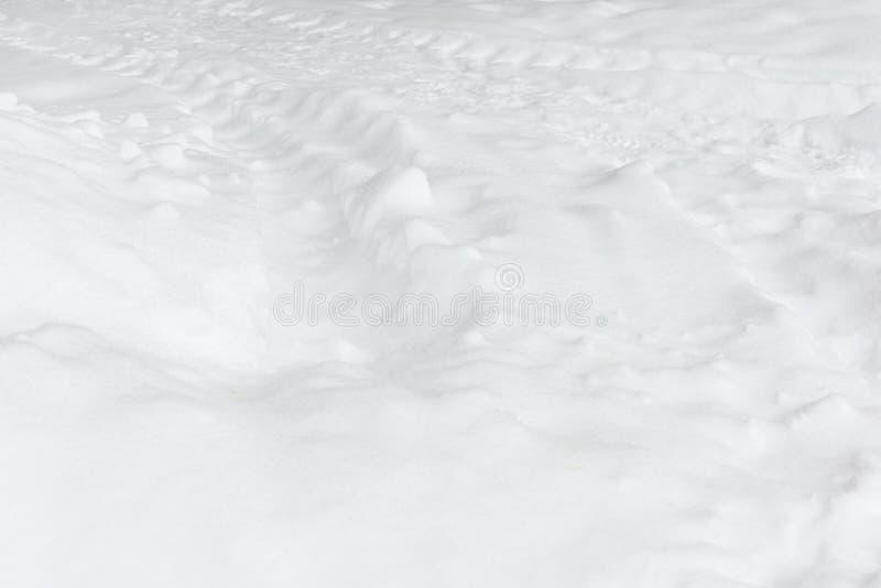 Świeży biały śnieg z śladami od ciągnika Abstrakcjonistyczny tło z śnieżną teksturą zdjęcie stock