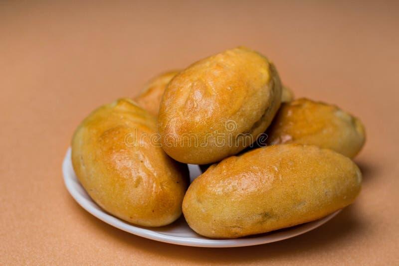 Świezi paszteciki z mięsem, kapustą lub jakaś plombowaniem, Piec kulebiaki w piekarniku Na białym talerzu obrazy stock