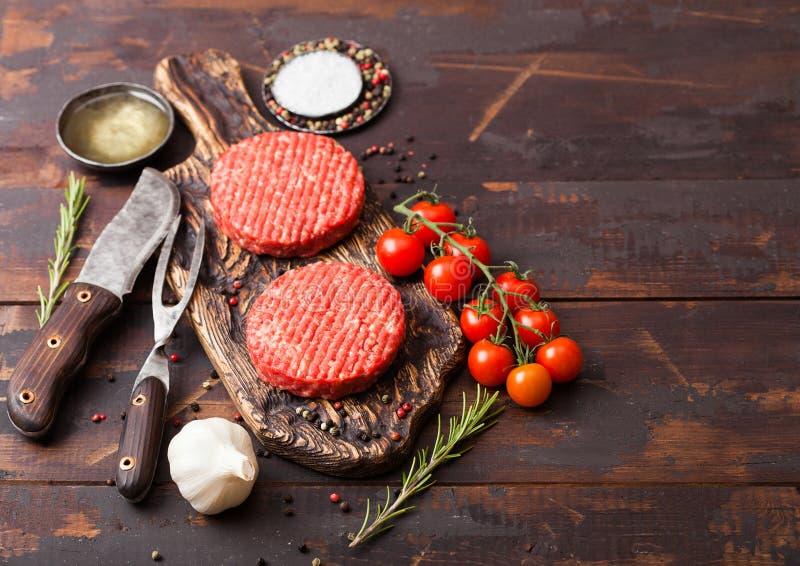 Świezi surowi minced domowej roboty rolnicy piec na grillu wołowina hamburgery, rozwidlają z nożem na drewnianym i pikantność i z zdjęcie royalty free
