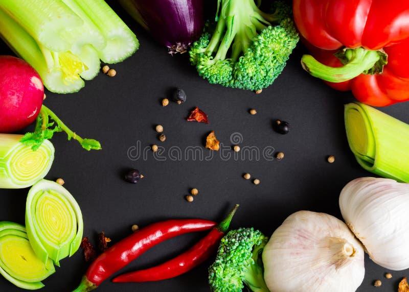 Świezi warzywa na czarnym tle: brokuły, seler, leek, czerwona cebula, chili pieprz, słodki czerwony pieprz, rzodkwie i czosnek, zdjęcie royalty free