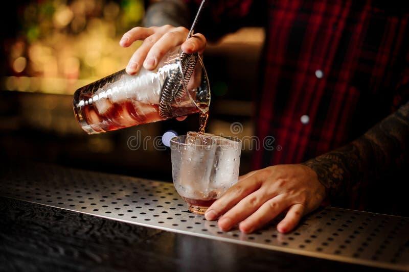 倾吐从量杯的侍酒者一个Vieux Carre鸡尾酒 图库摄影