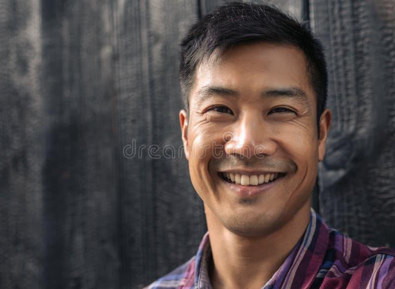 倾斜对黑木墙壁的快乐的年轻亚裔人 免版税图库摄影