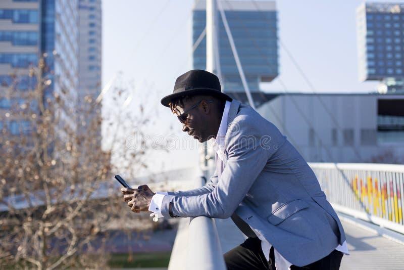 倾斜在金属篱芭的一个非洲黑人年轻人佩带的帽子和太阳镜的侧视图,当使用一个手机户外时 免版税库存照片