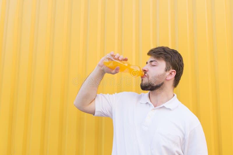 喝从一个瓶的帅哥橙味饮料在黄色墙壁的背景 库存照片