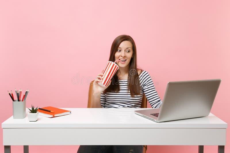 喝从有可乐苏打的plactic杯子的激动的妇女工作坐项目在办公室在有当代的白色书桌 免版税图库摄影