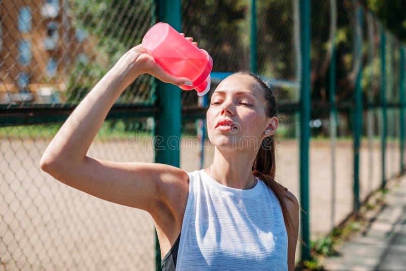 喝从瓶的运动的年轻性感的妇女画象凉水在一个夏天运动场户外 免版税库存图片