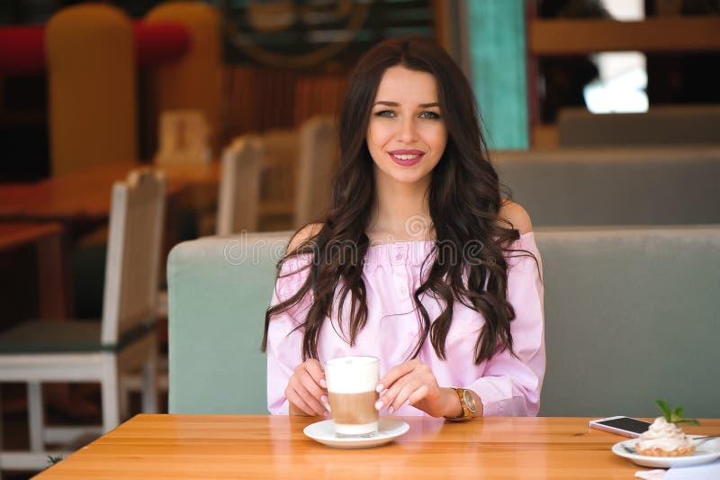 喝热的热奶咖啡咖啡和吃蛋糕的妇女在咖啡馆 图库摄影