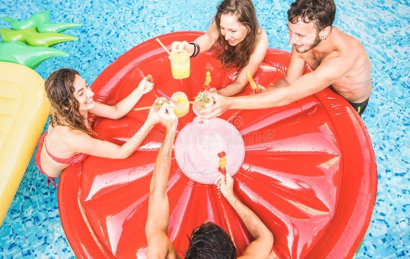 喝鸡尾酒的愉快的朋友顶视图在游泳场党-与愉快的获得人和的女孩的假期概念乐趣 免版税图库摄影