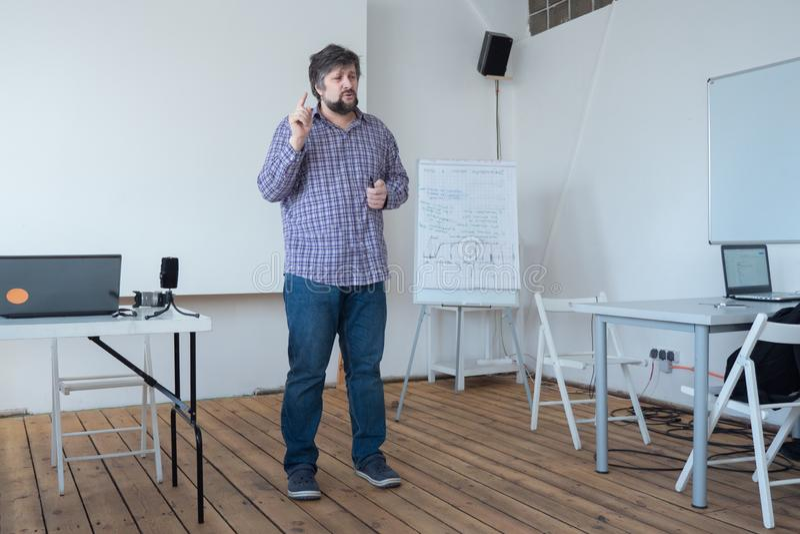 咨询新的专家的老练的工作者 创新者谈话与观众 谈话与观众在教室 库存照片