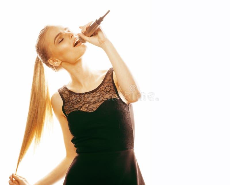 唱歌在话筒的年轻人相当白肤金发的妇女隔绝了紧密卡拉OK演唱 免版税库存照片