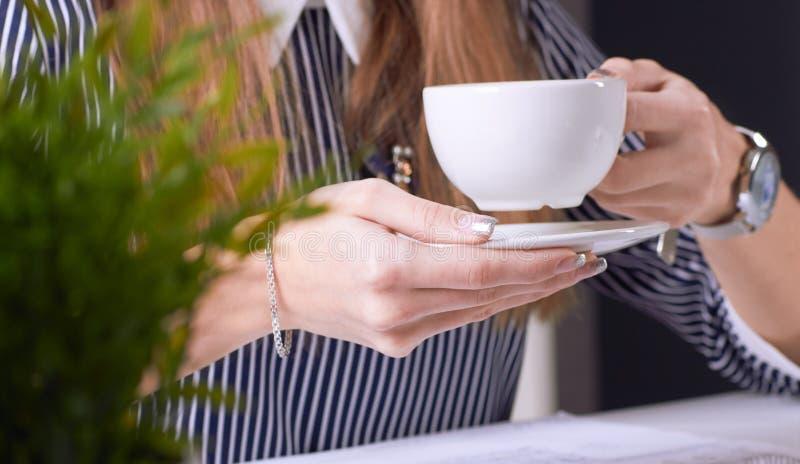 咖啡杯在女实业家的手上 年轻女人与文件和膝上型计算机特写镜头一起使用 免版税库存照片