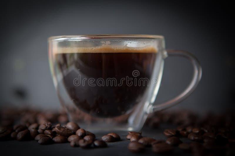 咖啡杯用新鲜的煮的咖啡和棕色烤咖啡豆 免版税库存照片