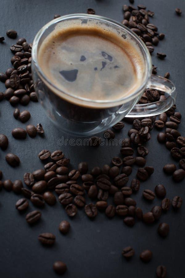 咖啡杯用新鲜的煮的咖啡和棕色烤咖啡豆 库存图片