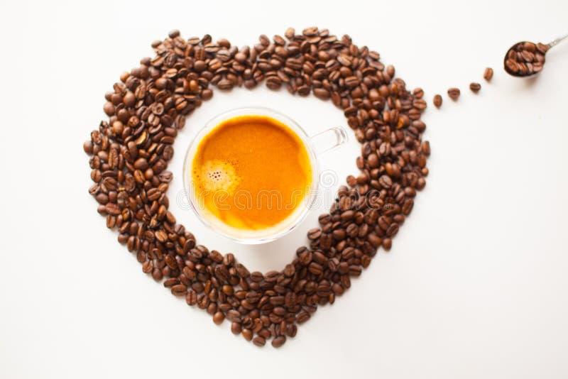 咖啡杯用新鲜的煮的咖啡和棕色烤咖啡豆 免版税库存图片