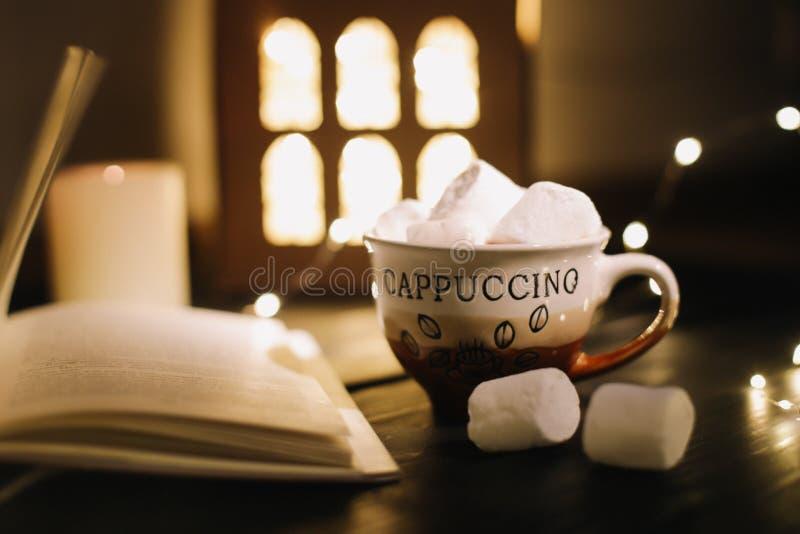 咖啡杯用蛋白软糖和一本书在桌上 在黑暗的背景,平的位置的静物画 库存图片