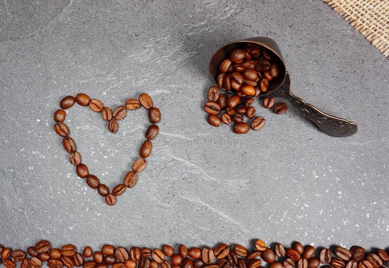 咖啡豆疏松与匙子的公平交易和心脏在厨房worktop背景 库存图片