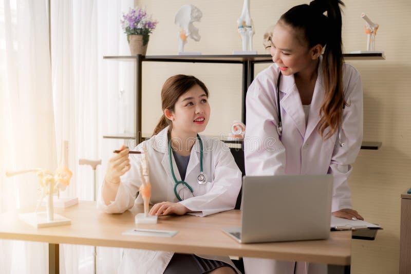 和工作坐书桌使用手塑料解剖学生理模型骨头的医生亚裔妇女和递指向或写n 免版税库存图片
